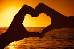 Image composée des couples faisant la forme de coeur avec des mains Image stock
