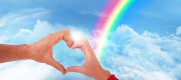 Image composée des couples faisant la forme de coeur avec des mains Photographie stock libre de droits