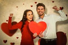 Image composée des couples gais tenant le coeur de papier Photographie stock
