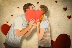 Image composée des couples geeky de hippie embrassant derrière la carte de coeur Photo stock