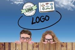 Image composée des couples geeky de hippie tenant l'affiche Photographie stock