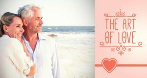 Image composée des couples heureux étreignant sur la plage regardant à la mer Photo stock