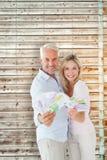 Image composée des couples heureux clignotant leur argent liquide Images libres de droits