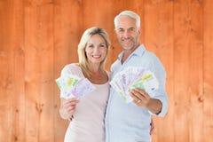 Image composée des couples heureux clignotant leur argent liquide Photographie stock libre de droits