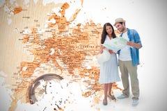Image composée des couples heureux de hippie regardant la carte Photo stock