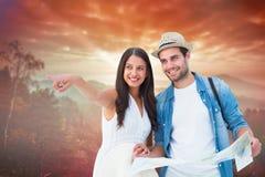 Image composée des couples heureux de hippie regardant la carte Photographie stock libre de droits