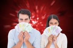 Image composée des couples heureux montrant leur argent Photos libres de droits