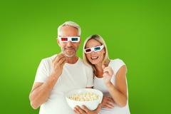 Image composée des couples heureux portant les lunettes 3d mangeant du maïs éclaté Photo libre de droits