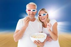 Image composée des couples heureux portant les lunettes 3d mangeant du maïs éclaté Photographie stock libre de droits
