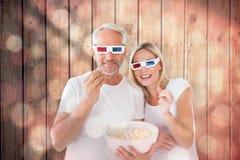Image composée des couples heureux portant les lunettes 3d mangeant du maïs éclaté Image libre de droits