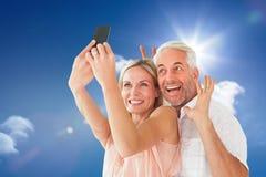 Image composée des couples heureux posant pour un selfie photographie stock libre de droits