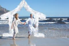 Image composée des couples heureux sautant nu-pieds sur la plage Image stock