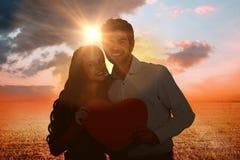 Image composée des couples heureux tenant le coeur de papier Photo libre de droits