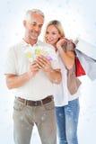 Image composée des couples heureux tenant les paniers et l'argent liquide Photographie stock libre de droits