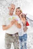 Image composée des couples heureux tenant les paniers et l'argent liquide Photo libre de droits