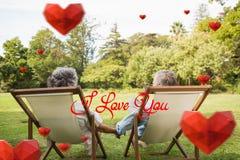 Image composée des couples mûrs heureux se reposant en parc Photographie stock