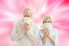Image composée des couples mûrs heureux souriant à l'appareil-photo montrant l'argent Photographie stock libre de droits