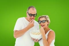 Image composée des couples mûrs portant les lunettes 3d mangeant du maïs éclaté Photographie stock