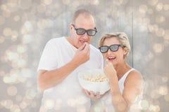 Image composée des couples mûrs portant les lunettes 3d mangeant du maïs éclaté Images libres de droits