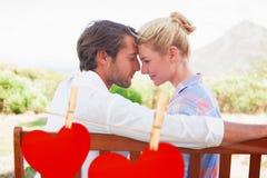 Image composée des couples mignons se reposant sur le banc souriant ensemble à l'un l'autre Photographie stock