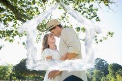 Image composée des couples mignons se tenant dans l'embrassement de parc Photos stock