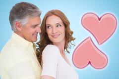 Image composée des couples occasionnels étreignant et souriant Photographie stock libre de droits