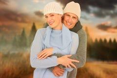 Image composée des couples occasionnels dans l'habillement chaud Image stock