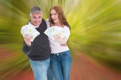 Image composée des couples occasionnels montrant leur argent liquide Photographie stock libre de droits