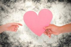 Image composée des couples passant un coeur de papier Image libre de droits