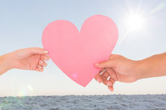 Image composée des couples passant un coeur de papier Images libres de droits