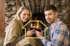 Image composée des couples romantiques grillant des verres à vin devant la cheminée allumée Image libre de droits