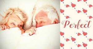 Image composée des couples supérieurs dans des mots de lit et de valentines Image stock