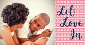 Image composée des couples sur des mots de lit et de valentines Image stock