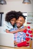 Image composée des couples sur l'ordinateur et des coeurs volant de la boîte 3d Photographie stock