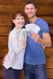 Image composée des couples tenant des fans d'argent liquide Photo libre de droits