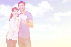 Image composée des couples tenant des fans d'argent liquide Photos stock