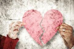 Image composée des couples tenant deux moitiés du coeur brisé Photo libre de droits