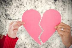 Image composée des couples tenant deux moitiés du coeur brisé Images libres de droits