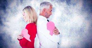 Image composée des couples tenant deux moitiés du coeur brisé Image stock
