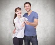 Image composée des couples tenant la fan de l'argent liquide Images stock