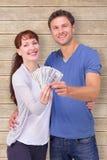 Image composée des couples tenant la fan de l'argent liquide Photo libre de droits