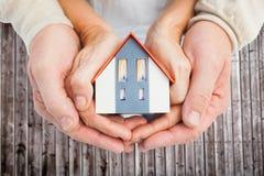 Image composée des couples tenant la maison de petit modèle dans des mains Image stock
