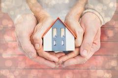 Image composée des couples tenant la maison de petit modèle dans des mains Images stock