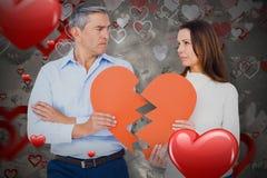 Image composée des couples tenant le papier 3D de forme du coeur brisé Image stock