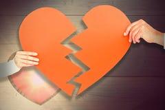 Image composée des couples tenant le papier de forme du coeur brisé Photo libre de droits