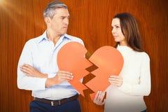 Image composée des couples tenant le papier de forme du coeur brisé Photographie stock