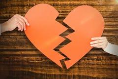 Image composée des couples tenant le papier de forme du coeur brisé Images libres de droits