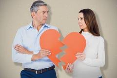 Image composée des couples tenant le papier de forme du coeur brisé Photos stock