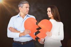 Image composée des couples tenant le papier de forme du coeur brisé Photos libres de droits