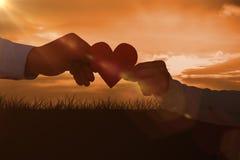 Image composée des couples tenant le papier de papier de forme de coeur Images stock